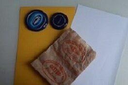 Na stole znajduję się żółta i biała kartka, dwie niebieskie nakrętki od słoików oraz papierowa torba