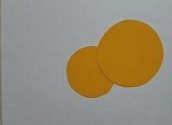 Na białej kartce znajdują się dwa żółte kółka - jedno małe, drugie duże.