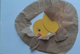 Na białej kartce znajduję się żółty kurczak w środku papierowej pisanki