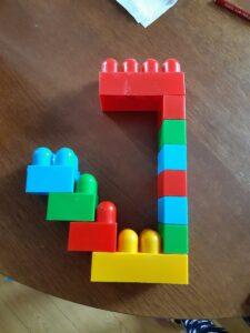 litera jot ułożona z kolorowych klocków