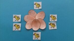 Na niebieskim tle znajduje się sześć brązowych jajek ułożonych w kształcie kwiatu oraz sześć żółtych kurczątek.