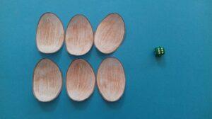 Na niebieskim tle znajduje się sześć brązowych jajek oraz zielona kostka do gry z sześcioma białymi kropkami