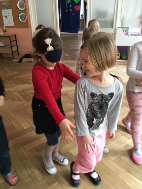 Dzieci bawiące się w parach. Jedna z dziewczynek stoi przed drugą i spogląda na nią. Druga ma założoną opaskę na oczy.