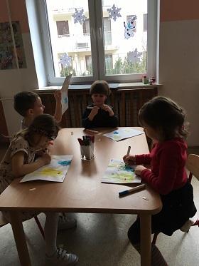 Dzieci siedzące przy stoliku i rysujące coś flamastrami na kartkach papieru, na których znajduję się farba. Jeden chłopiec trzyma kartkę w górze.