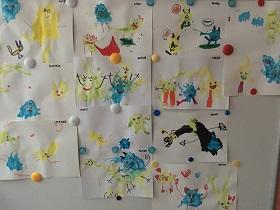 Prace plastyczne dzieci, wiszące na tablicy, przyczepione magnesami. Na pracach znajdują się kleksy z farb oraz narysowane na nich minki flamastrami.