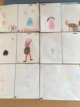 Prace plastyczne dzieci narysowane kredkami i przyczepione do tablicy korkowej. Na pracach widnieją głównie koty i postaci.