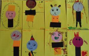 Prace plastyczne dzieci przedstawiające skrzaty, wiszące na tablicy magnetycznej.