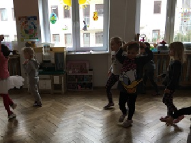 Dzieci stojące w sali na podłodze i wykonujące różne figury swoim ciałem.