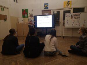 nauczycielka stoi przy monitorze i tłumaczy coś koleżankom