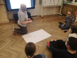 nauczycielka klęczy przed kartonem. Nauczycielki siedzą na około i słuchają