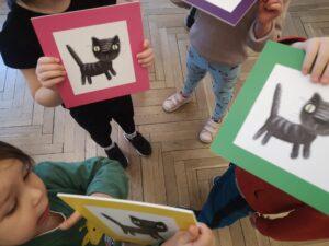 dzieci pokazują swoje ilustracje, na których są koty