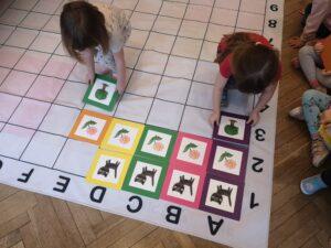 dwie dziewczynki układają na macie ilustracje