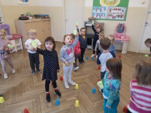 dzieci stojące pomiędzy kubeczkami rozłożonymi na podłodze