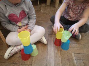 dwie dziewczynki budują z kubeczków