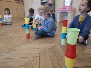 dzieci siedzą w siadzie skrzyżnym, a przed nimi wieże z kubeczków