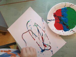 kartka papieru, obok talerzyk z farbą