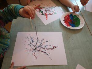 dwie kartki papieru, widać ręce dzieci trzymające nitkę umoczoną w farbie