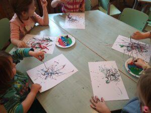 dzieci siedzące przy stoliku, każde maluje nitką zamoczoną w farbie
