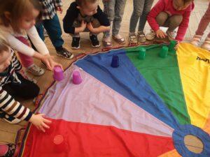 dzieci układają kubeczki na kolorowej chuście