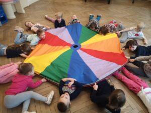 dzieci leżące pod chustą animacyjną
