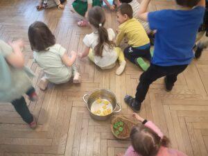 Dzieci na podłodze zbierają do garnka żółte i zielone klocki