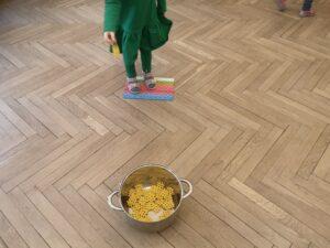 Dziewczynka stoi na kolorowych klockach i rzuca klockiem do celu do garnka