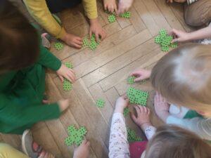 Dzieci na podłodze układają zielone klocki