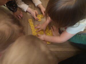 Dzieci na podłodze układają żółte klocki