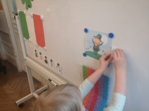 Dziewczynka przyczepia ilustracje do tablicy