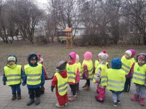 Dzieci stoją na tle parku w kamizelkach odblaskowych