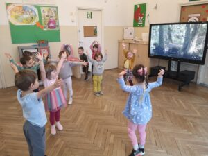 dzieci bawią się w sali, mają uniesione ręce, udają drzewa