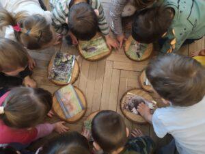 dzieci w kole oglądają ilustracje zwierząt leśnych