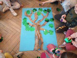 dzieci siedzą na około drzewa z papieru i zielonych koniczynek