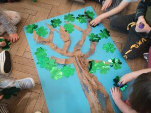 dzieci oglądają papierowe drzewo na kartonie