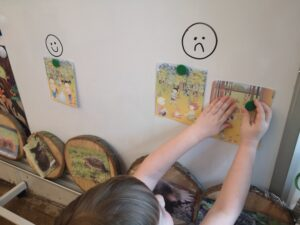 dziewczynka przyczepia do białej tablicy ilustrację jak prawidłowo zachowywać się w lesie