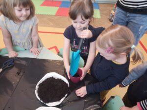 troje dzieci wspólnie sadzi cebulkę w doniczce. Jedna dziewczynka trzyma doniczkę, druga nakłada ziemię