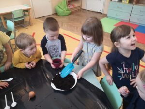 dzieci na około stołu patrzą jak dziewczynka nakłada łopatką ziemię do doniczki
