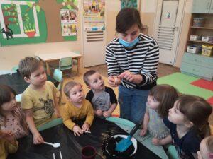 Pani pokazuje dzieciom cebulkę. Dzieci zgromadzone przy stoliku na około niej obserwują.