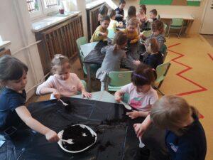 dzieci siedzą przy stolikach i nakładają ziemię do doniczek