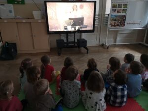 dzieci siedzą na przeciwko monitora i oglądają koncert online