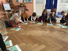 Dzieci siedzące na podłodze w kółku, w siadzie skrzyżnym. Przed nimi leżą książki, które oni wskazują palcem.