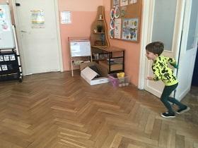 Dziecko znajdujące się w sali, trzymające w ręku zielony woreczek. Przygotowujące się do biegu.
