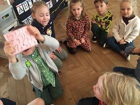 Dzieci siedzące w siadzie skrzyżnym na podłodze w kółku. Jedno z dzieci trzyma kartkę z czarnymi znakami zapytania.