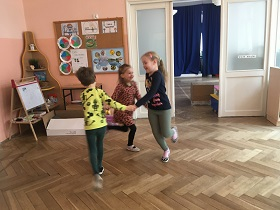 Trójka dzieci tańcząca w kółku w sali i trzymająca się za ręce.