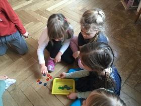 Dzieci siedzące na podłodze w sali. Przed nimi leży żółte pudełko z kolorowymi żetonami.