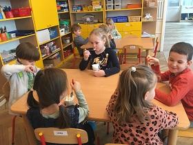 Dzieci siedzące przy stolikach. Przed nimi stoją kubeczki z galaretką i łyżeczką. Część dzieci trzyma łyżeczkę w buzi.