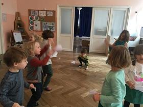 Dzieci stojące na podłodze w dwóch rzędach naprzeciwko siebie. Zwrócone są do siebie twarzami. W rękach trzymają wachlarze z papieru.