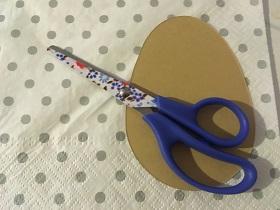 Na białej serwetce w szare kropki znajduje się szablon jajka oraz nożyczki z niebieskimi rączkami oraz nożycami w kwiatki