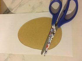 Na stoliku znajduje się kartka papieru z położonym na niej szablonem jajka oraz nożyczkami z niebieskimi rączkami i kwiatowymi nożycami