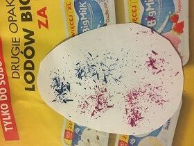 Na gazecie znajduje się biały szablon jajka z różowymi i niebieskimi wiórkami z kredki